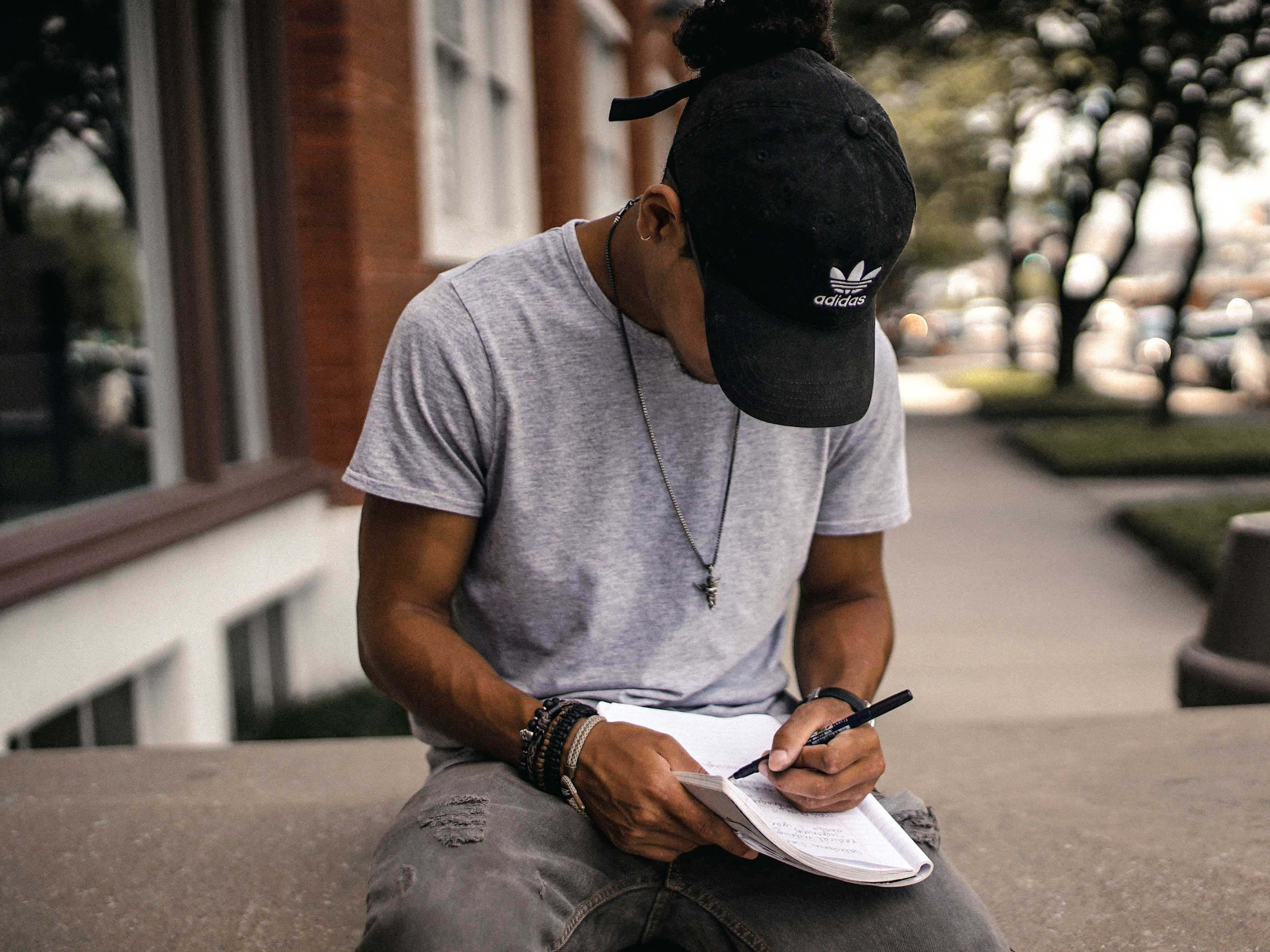 Young man takes notes outside a building