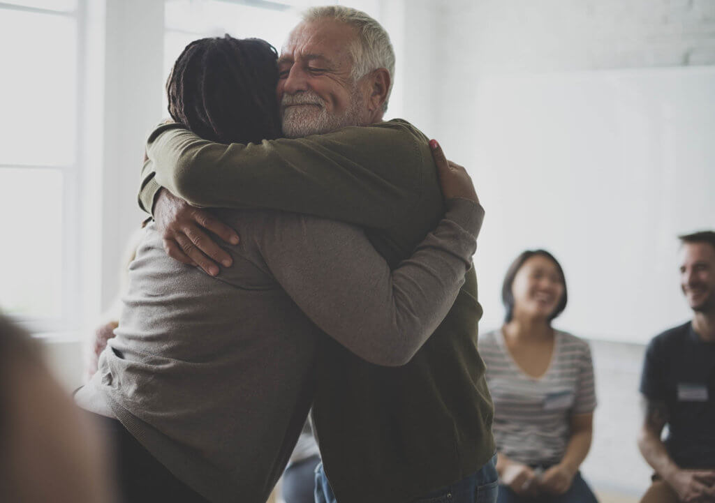 Old man hugs person in support circle