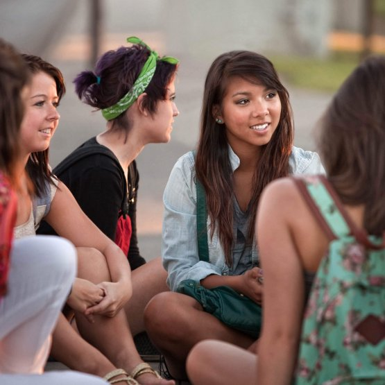 Diverse group of female friends sit on the ground