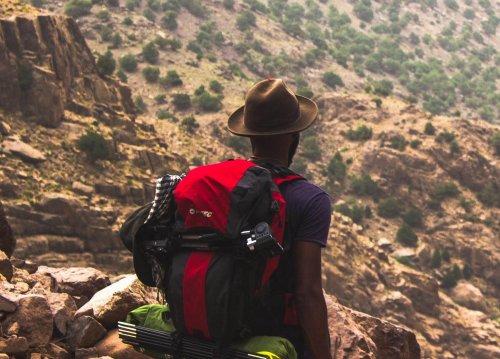 Man overlooks hillside view on a hike