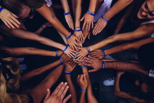 Diverse group of people put their hands together in a circle to embody teamwork